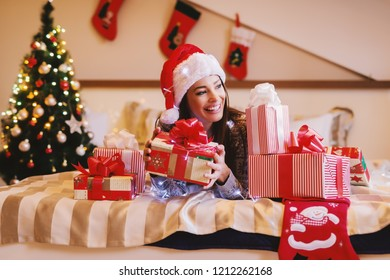 Beautiful brunette with santa's hat on head posing in bed surrounded by Christmas presents. Christmas holidays concept.