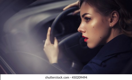 Beautiful brunette sexy spy agent (killer or police) woman in jacket driving a car after someone, to catch him