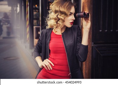 Beautiful brunette sexy spy agent (killer or police) woman in leather jacket and red luxury dress with a binocular in her hand stalking someone, to catch him in european city