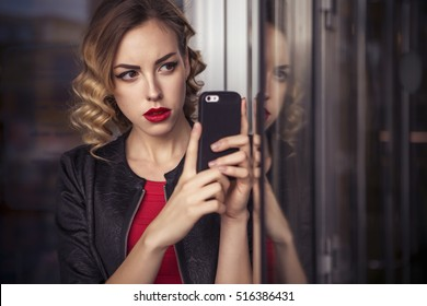 Beautiful brunette sexy spy agent (killer or police) woman in leather jacket and red luxury dress with a phone in her hand watching after someone, make business work phone calls in european city