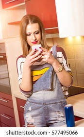 Beautiful brunette in short texas jeans cooking. Modern red colored design kitchen. Smiling young girl cooking. Texting on the phone.
