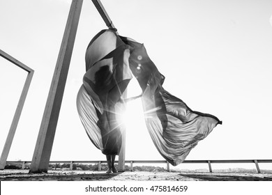 Beautiful brunette silk dancer with red curtains posing at rooftop
