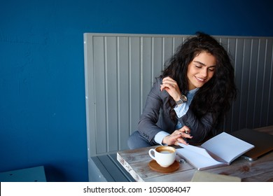 Beautiful brunette sitting in coffee shop and working on computer.