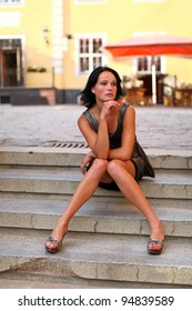 Beautiful brunette is sitting in sexual pose on the steps on the street of Old Riga, Latvia. She is a little bit sad and also dreaming about something against old barracks and cafe at summer day.