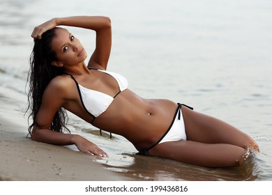 beautiful brunette sitting in water on the coast