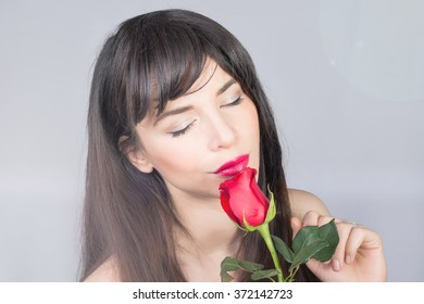 Beautiful brunette smelling a red rose