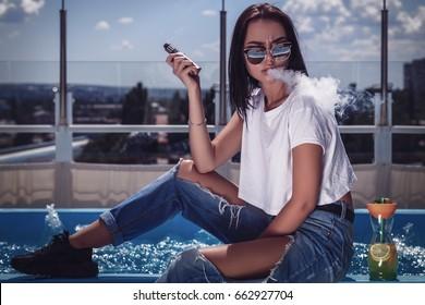 Beautiful brunette smoke electronic cigarette on the summer terrace of restaurant.Swimming pool