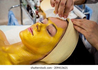 Beautiful brunette in a spa salon. Girl taking facial treatment at the salon. Facial treatment, gold mask, beauty, spa, mask - Concept of facial skin care. Article about Beauty.