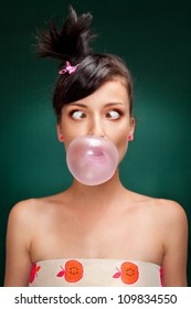 a beautiful brunette with squint eyed blowing a bubblegum on a green background