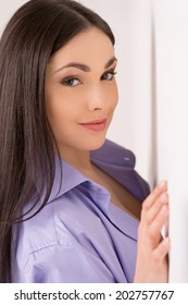beautiful brunette standing near white wall. closeup of young woman looking and smiling