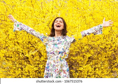 Beautiful brunette is standing with open arms surrounded by yellow flowers. Spring welcome.