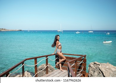 Beautiful brunette standing in a swimsuit with an inflated waist on a wooden pier on the seashore