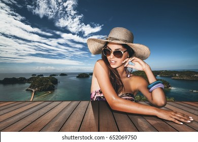 Beautiful brunette with straw hat and sunglasses in a tropical island background