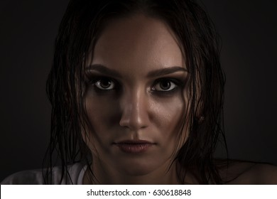 Beautiful brunette in studio on gray background. Drama