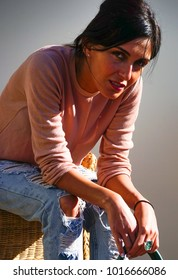 Beautiful brunette stylish woman sitting on chair