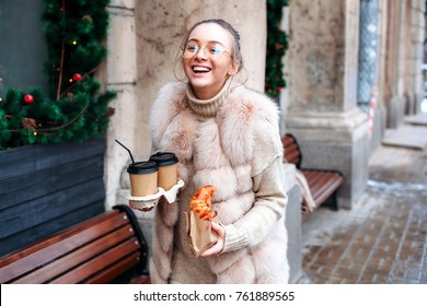 Beautiful brunette stylish woman are walking on the street having coffee and croissants in hans and smiling feeling happy