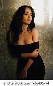 Beautiful brunette taking off stylish classy black dress posing alluringly.