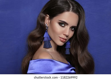 Beautiful brunette with tassel earrings over blue. Jewelry bijouterie Fashion. Sensual Woman with shine wavy hair style and evening makeup In Luxury Jewels. Beauty make-up portrait.
