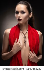 Beautiful brunette topless girl model, covering her naked breast with a red scarf and wearing a modern necklace on the deep decollete. Copy space. Advertising and commercial design. Healthy clean skin