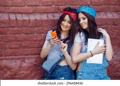 Beautiful brunette twins girls. With tablet and smart phone on brick wall background. Together looking at smart phone. Wearing jeans overalls, red and blue bandanas and white top. Copy space.