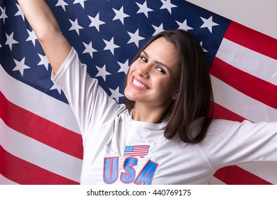 Beautiful brunette USA fan girl holding flag