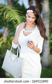 Beautiful brunette using her smartphone outside
