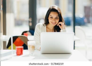 Beautiful brunette using laptop in cafe