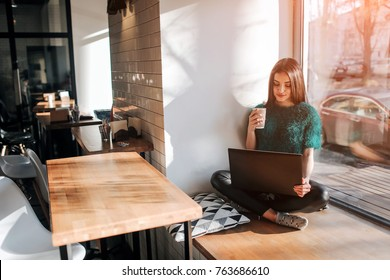 Beautiful brunette using laptop in cafe. Young attractive woman is making plans for the future, sitting in front of an open laptop computer in a cozy coffee shop.