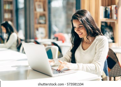Beautiful brunette using notebook in cafe