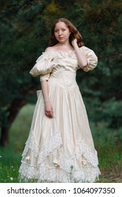 Beautiful brunette in a vintage dress. A nice young girl in a classic outfit. A woman in a stylish vintage dress. Style of the queen. Classical attire of the princess. A woman is walking in the woods.