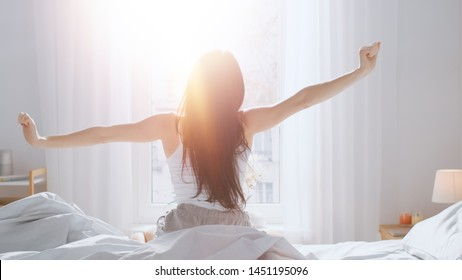 Beautiful Brunette is Waking up in the Morning, Stretches in the Bed, Sun Shines on Her From the Big Window. Happy Young Girl Greets New Day with Warm Sunlight Flare. - Shutterstock ID 1451195096