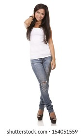 beautiful brunette wearing white top and jeans on light background