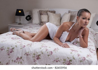Beautiful brunette in white lying on her bed