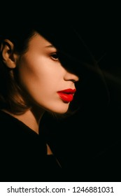 Beautiful brunette womam posing in costume and hat on black. Model, portrait, natural emotion white skin red lips