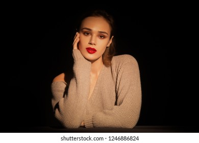 Beautiful brunette womam posing in sweater on black. Model, portrait, natural emotion white skin red lips