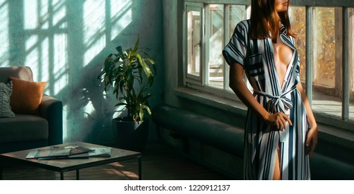 beautiful brunette womam wear white and black long dress. Female unties the belt and stands against sunny window