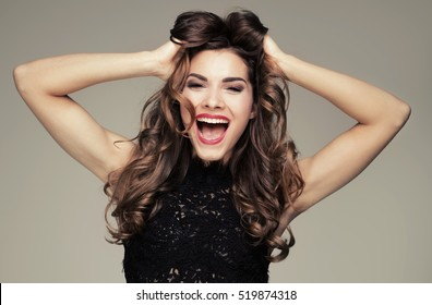 Beautiful brunette woman with amazing toothy smile. Emotions. Happiness. Studio shot.