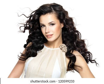 Beautiful brunette woman with beauty long curly hair. Fashion model with wavy hairstyle