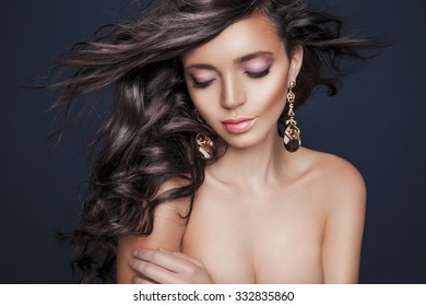 Beautiful brunette woman with beauty long curly hair and colorful makeup. Pink Lips. Fashion model with wavy hairstyle. Toned in warm colors. Studio shot, horizontal