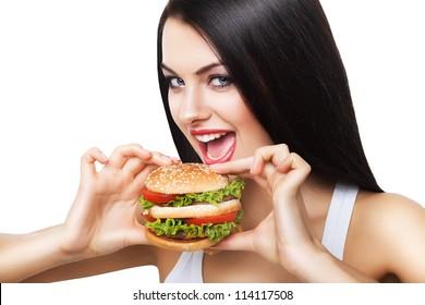 beautiful brunette woman biting hamburger on white background