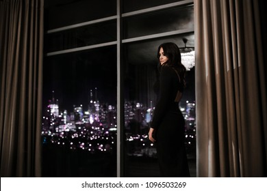 beautiful brunette woman in a black dress is standing near a panoramic window overlooking the lights of a nightly New York city and looking into the distance