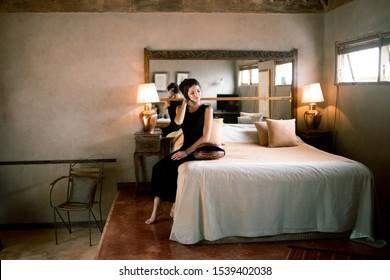 Beautiful brunette woman in black peignoir dress relaxing on king size bed in vintage bedroom. Boudoir girls morning. Wedding preparations.