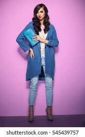 Beautiful brunette woman in a blue coat and nice top, holding a purse. Fashion spring autumn winter photo