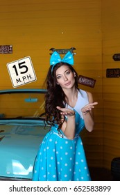 Beautiful brunette woman in a blue dress with polka dots with a bow on her head looking into the camera sends an air kiss standing near the blue car