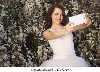 Beautiful brunette woman bride in a garden park in white wedding dress, curly hairstyle and a smile make selfie on a mobile phone. warm weather, outdoors. copy space