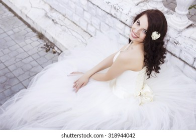Beautiful brunette woman bride in a garden park in white wedding dress, curly hairstyle and a smile. warm weather, outdoors. copy space