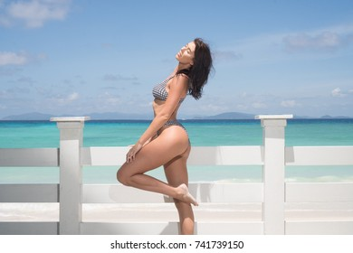 Beautiful brunette woman in checked bikini smiling while standing close to white wooden fence on the sandy beach of paradise island over blue sea and sky background