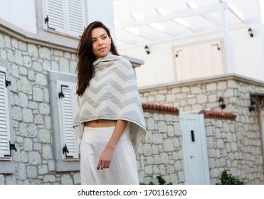 beautiful brunette woman in chic white loose pants and covered herself with a shawl, posing in front of a house.