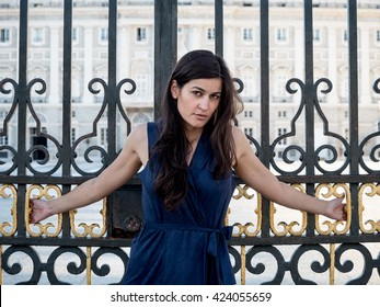 Beautiful brunette woman crucified on a palace's gate (luxury's attachment concept)