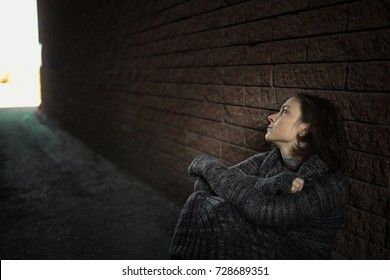 beautiful brunette woman in a dark sweater near a brick wall, concept of loneliness and depression, selective focus, dark style